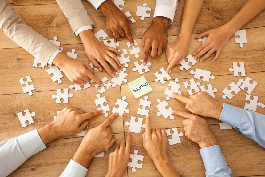 A group of people putting a jigsaw puzzle together.